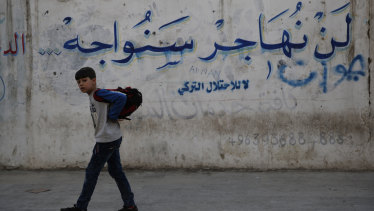 "A Syrian student walks next a wall with Arabic that reads: ""We will not emigrate we will confront, no to the Turkish occupation,"" in Manbij, north Syria. On  December 28, 2018, Syria's military said it entered the flashpoint Kurdish-held town of Manbij, where Turkey has threatened an offensive. a claim that was refuted by US  troops who patrol the town. The conflicting reports reflect the potential for chaos in the wake of the US surprise decision to withdraw troops from Syria."