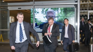 AFP officers leave the ABC Sydney building on Wednesday evening.
