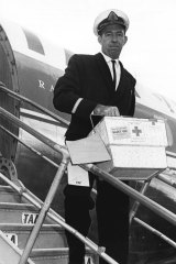 First batch ... Mr Noel Murphy from TAA hurries the blood package down the steps of an airliner.