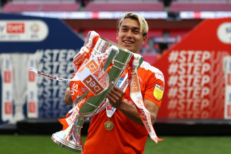 Dougall holds up the trophy after Blackpool's promotion.