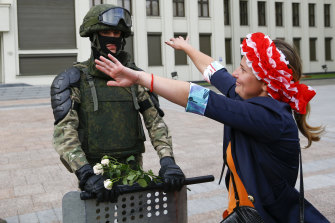 A woman runs to embrace a soldier guarding a Belarusian government building in Minsk.