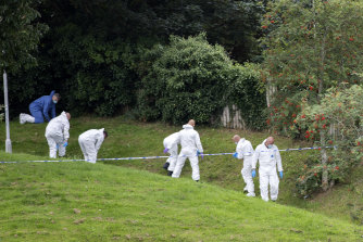 Forensic teams search a grassed area near one of the shooting scenes.
