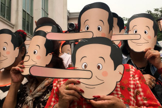 Pro-democracy activists wearing masks mock Thailand's Prime Minister Prayuth Chan-ocha.