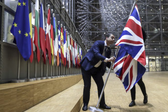 A member of protocol removes the Union flag from the atrium of the Europa building in Brussels on January 31, 2020.