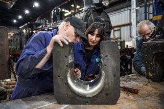 Volunteers from Mornington Rail repairing locomotive parts at the workshops.