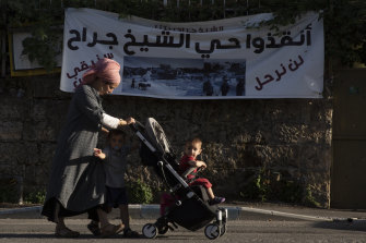 "A Jewish settler and her children walk in Sheikh Jarrah. The banner in Arabic reads: ""Sheikh Jarrah neighbourhood - we will not leave - we will remain steadfast."""