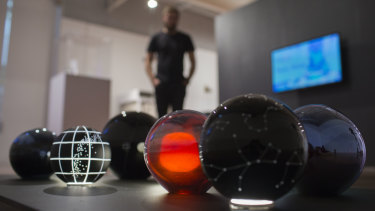 A visitor views Emeirely Nucifora-Ryan's constellation themed glass globes at the ANU School of Art and Design 2018 Graduating Exhibition.