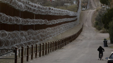 A boy rides his bike along a razor-wire-covered border wall that separates Nogales, Arizona, from Nogales, Mexico.