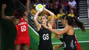 Te Paea Selby-Rickett of New Zealand, centre, and Ama Agbeze of England, left, compete during the preliminary round netball game.