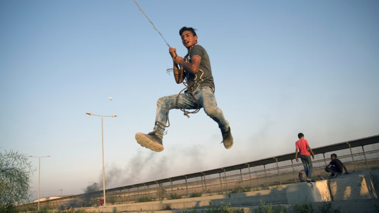 A Palestinian protester swings from a hanging metal cable during a protest at the entrance of Erez border crossing between Gaza and Israel, in the northern Gaza Strip last week.