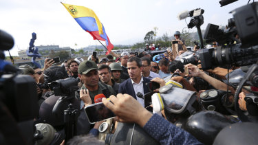 Venezuela's opposition leader Juan Guaido, centre, stands with an unidentified military officer who looks to be helping to lead a military uprising.