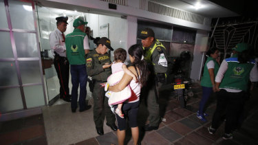Police attend to 17-year-old Venezuelan Eliusmar Guerrero and her 18-month-ols daughter at a child welfare office where she can get food and a temporary place to sleep in Cucuta, Colombia.