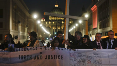 Survivors of sex abuse hold a cross on Via della Conciliazione, the road leading to St Peter's Square, during a twilight vigil for victims of sex abuse.