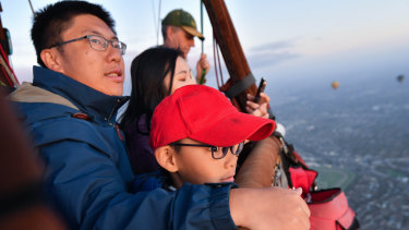 Chinese tourists Wei Chen and Zhu Yi Qi with their son Zhu Si Yun, fly in a hot air balloon over Melbourne.