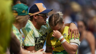 Devastated: Emma Tonegato is comforted after Australia's six-try loss to Canada.