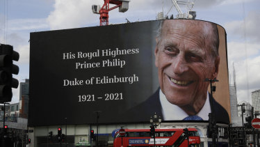 A tribute is projected onto a large screen at Piccadilly Circus in London.