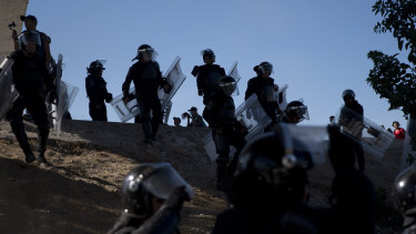 Mexican police spread out as they try to keep migrants from getting past the Chaparral border crossing in Tijuana.