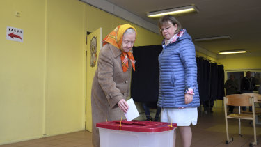 An elderly Latvian woman casts her ballot papers at a polling station in Riga, Latvia, on Saturday.