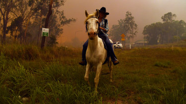 Rhonda Anderson moves herself and her horse to safety near Mount Larcom.