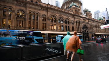 Pedestrians are seen in the CBD during a thunderstorm in Sydney on Saturday
