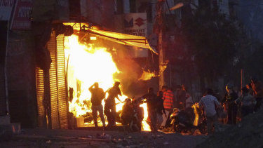 A shop is set on fire during violence between two groups in New Delhi, India.