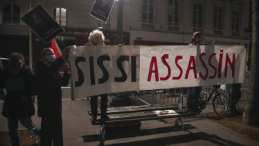People hold a banner that reads, 'Sissi killer,' as they stage a protest against the Egyptian President Abdel-Fattah el-Sisi by the National Assembly in Paris.