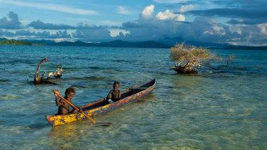 Boys fish in the Marovo Lagoon in the Solomon Islands.