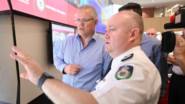 Prime Minister Scott Morrison is briefed by NSW RFS Commissioner Shane Fitzsimmons in the NSW Rural Fire Service control room in Sydney on Sunday.