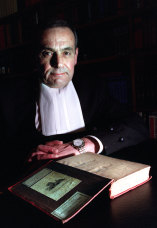 Justice David Levine AO RFD QC, inspects a book originally in the personal library of Charles Dickens.