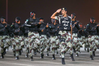 """Saudi security forces parade on the eve of the Haj. The writing on the officer's chest reads """"serving you is an honour for us""""."""