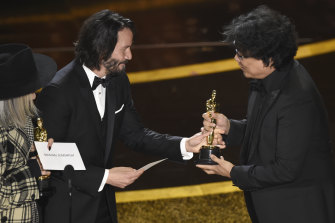 Keanu Reeves presents the Oscar for best original screenplay to Bong Joon Ho for Parasite.