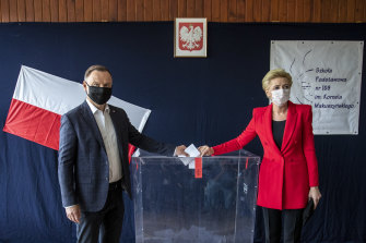 Incumbent Andrzej Duda, left, and his wife Agata Kornhauser Duda cast their votes in Poland's presidential election on Sunday.