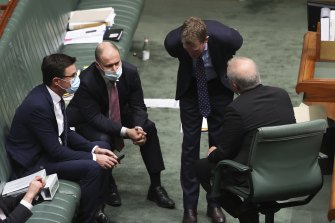 Prime Minister Scott Morrison and members of his cabinet consult during question time.
