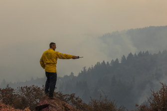 A firefighter with the California Office of Emergency Services monitors spot fires on Big Ridge, seen smoldering in the background, during the Walbridge portion of the LNU Lightning Complex fire in Sonoma County, California.