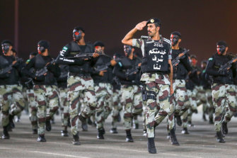 "Saudi security forces parade on the eve of the Haj. The writing on the officer's chest reads ""serving you is an honour for us""."