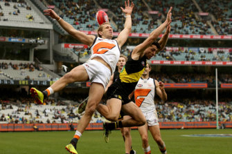 Taken out: Giant Nick Haynes cops a knock from Tigers' Jason Castagna.