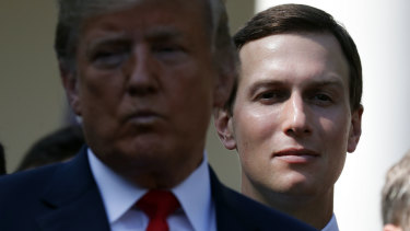 White House senior adviser Jared Kushner, right, stands behind President Donald Trump.
