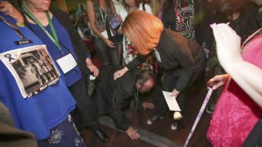 A man, Frank, falls to his knees as he meets Ms Gillard.