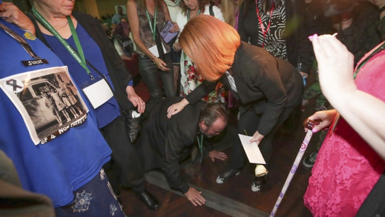 A man, Frank, falls to his knees as he meets Ms Gillard.