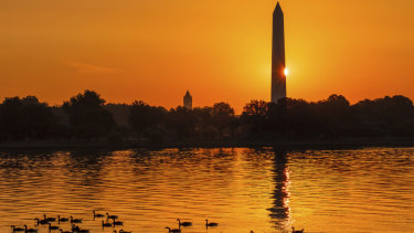 The sun peaks around the Washington Monument as geese float down the Potomac River in Washington as a hot day breaks on Sunday.