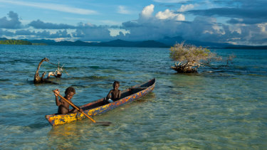 Boys fish in the Marovo Lagoon in the Solomon Islands.