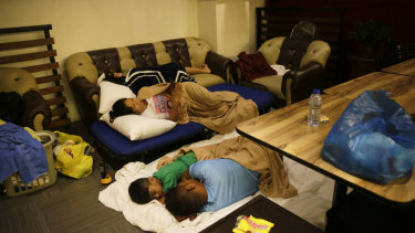 Guests sleep inside a hotel restaurant after the roof of their room was partly damaged due to strong winds from Typhoon Mangkut in Tuguegarao.