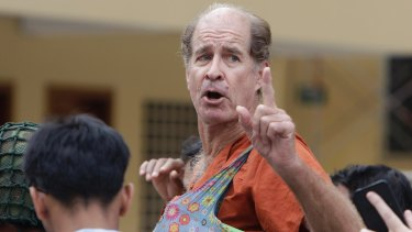 Australian filmmaker James Ricketson gestures as he is escorted by prison guards at the Cambodian Supreme Court in Phnom Penh, Cambodia.