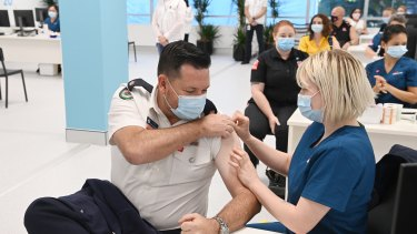 Ben Shepherd from the NSW Rural Fire Service receives his COVID-19 vaccine at the Olympic Park Vaccination Centre.