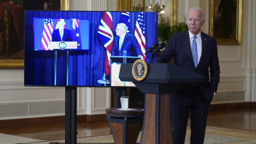 President Joe Biden, joined virtually by Australian Prime Minister Scott Morrison, right on screen, and British Prime Minister Boris Johnson, speaks about a national security initiative from the East Room of the White House.