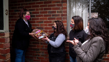 Eltham resident Jess Hoyle gets a care pack from Bec Russell, Jennifer Niehues, Patricia Callinan.