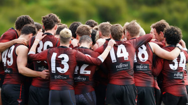 Essendon players form a huddle at training on Wednesday.