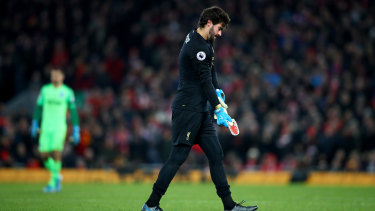 Alisson Becker of Liverpool leaves the pitch after his dismissal.