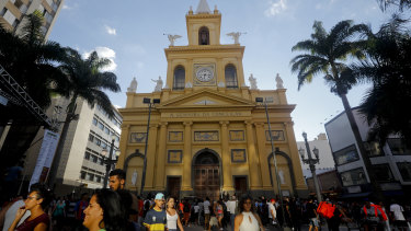 People walk outside the Metropolitan Cathedral after the fatal shooting in Campinas, Brazil.