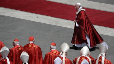 Pope Francis walks past cardinals after celebrating a Pentecost Mass in St Peter's Square at the Vatican on Sunday.